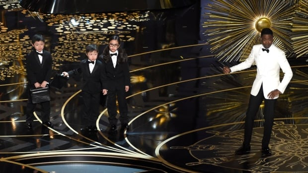 Host Chris Rock, right, sparked widespread criticism for his skit with Asian children at the Oscars on Sunday.