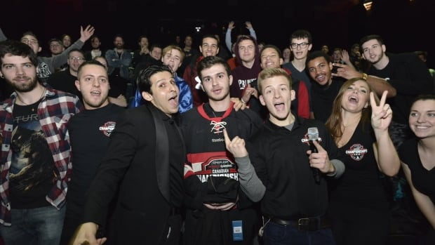 Matt Faithfull, centre, poses for the crowd at Toronto's Scotiabank Theatre after winning the regional qualifying tournament in the inaugural Call of Duty Canadian Championships. He'll return to the theatre on Sunday for the finals.