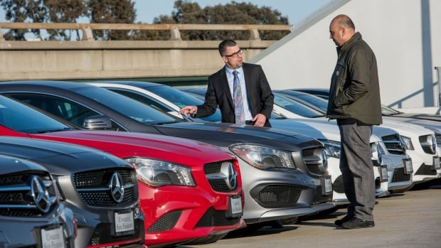 A salesman helps a customer browsing a Mercedes dealership in California. According to an analysis of government data, people who live next to lottery winners are more likely to go bankrupt due to spending beyond their means.