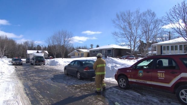 A fire fighter outside the home on Van Tassel St. in Bathurst, where the fatal fire occurred.