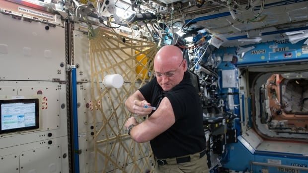 NASA astronaut Scott Kelly gives himself a flu shot on board the International Space Station as a part of an ongoing study on the human immune system in space on Sep. 24, 2015.
