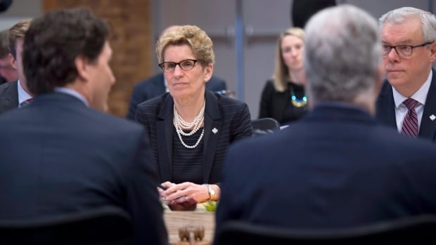 Ontario Premier Kathleen Wynne, centre, and Manitoba Premier Greg Selinger, right, listen to Prime Minister Justin Trudeau during the during a First Ministers Meeting in Vancouver, B.C.