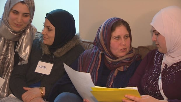 A group of women gather in an apartment in Coquitlam to learn English from volunteers with the Muslim Food Bank.