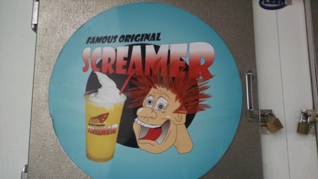 An ice machine with a decal advertising the screamer, outside a former Mr. G that is now a convenience store.