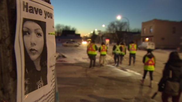 Winnipeg's Bear Clan Patrol put up posters in the North End on Thursday night. Delaine Copenace lived in Kenora but was known to visit friends and family in Winnipeg.