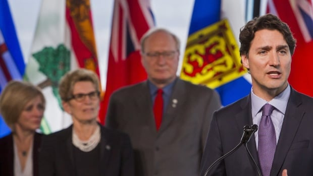 Prime Minister Justin Trudeau, with P.E.I. Premier Wade MacLauchlan in the background, speaks to media during the first ministers meeting held in Vancouver Thursday.