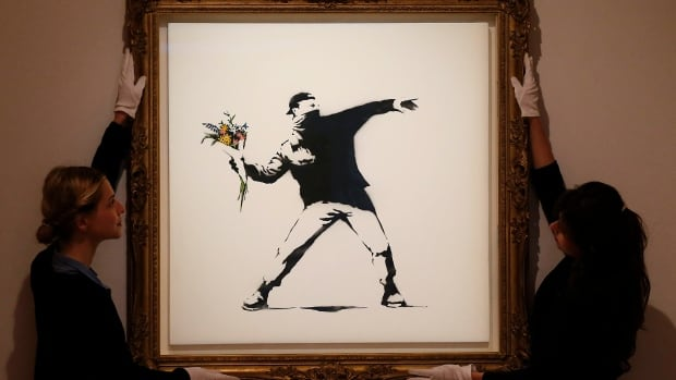 Auction house employees adjust a spray paint work by urban artist Banksy. Scientists have applied geographic profiling, a type of modelling used to track down criminals or map disease outbreaks, to identify the graffiti artist, whose real name has never been confirmed.