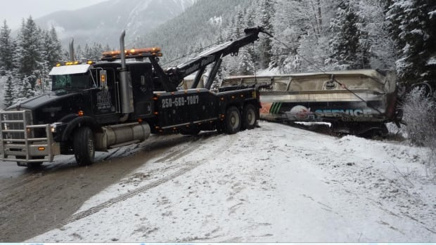 A tow truck pulls out one of the two tanker trailers.