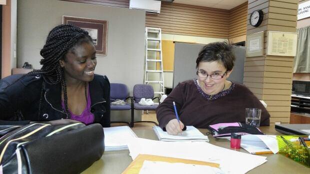 Fernande Endomo, mentor (left) helping Carly Dewitt learn French.