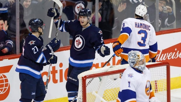 Winnipeg Jets' Nikolaj Ehlers (27) and Mark Scheifele (55) celebrate Scheifele's goal against New York Islanders goaltender Thomas Greiss (1) and Travis Hamonic (3) during first period NHL action in Winnipeg on Thursday, March 3, 2016.