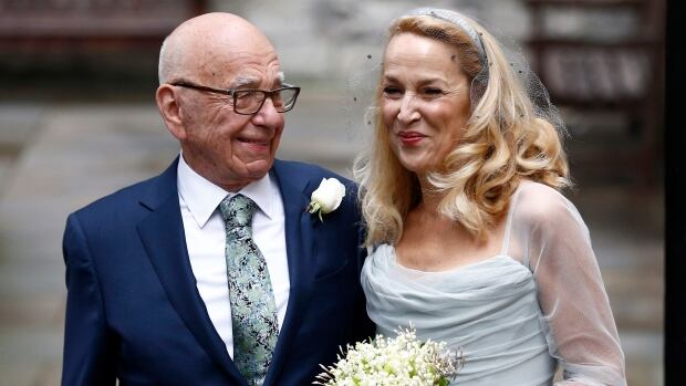 Rupert Murdoch and Jerry Hall pose for photographers outside St Bride's church following Saturday's a service.