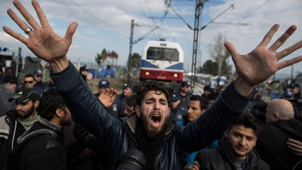 A refugee man pleads with a group of other men to calm down as a train attempts to pass at the Greek-Macedonia border on March 3, 2016 in Idomeni, Greece.