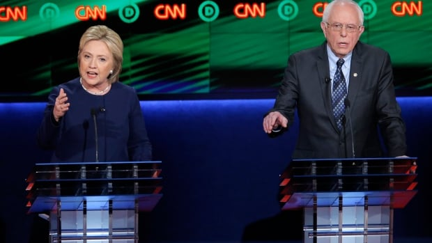 Democratic U.S. presidential candidates Hillary Clinton, left, and Bernie Sanders speak at the Democratic U.S. presidential candidates' debate in Flint, Mich., on Mar. 6, 2016.