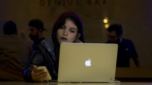 """A customer uses an iPhone and a Macbook computer at the Genius Bar in the Apple Store at Grand Central Station. Palo Alto Threat Intelligence Director Ryan Olson said the """"KeRanger"""" malware, which appeared on Friday, was the first functioning ransomware attacking Apple's Mac computers."""