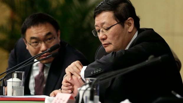 China's Finance Minister Lou Jiwei, right, says Beijing is expanding deficit spending to prevent a slide in growth and support its efforts to overhaul its cooling economy.