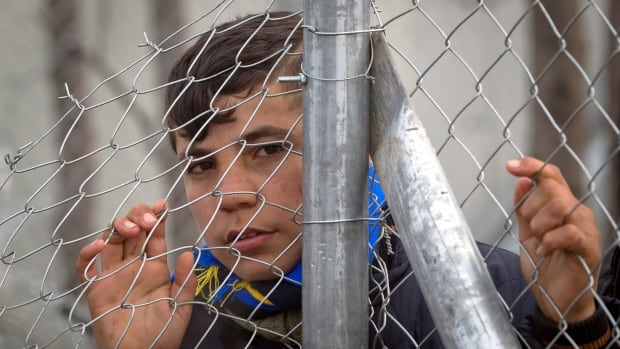 A migrant holds on to a fence near the border gate at the northern Greek border station of Idomeni, Tuesday. Up to 14,000 people are stranded on the outskirts of the village, with more than 36,000 in total across Greece, as EU leaders said they hoped they had reached the basis of a possible deal with Ankara to return thousands of migrants to Turkey.