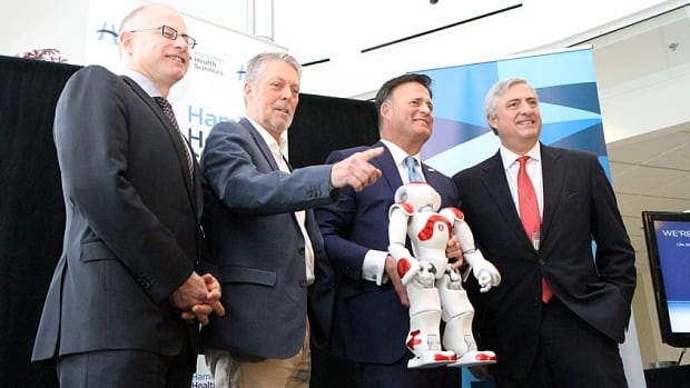 IBM and Hamilton Health Sciences announce a partnership that will see them move in to three floors of the Stelco Tower, also known as 100 King Street West, this year. From left are Bill Charnetski, Ontario's chief health innovation strategist; Mayor Fred Eisenberger; Dino Trevisani, president of IBM Canada, and Rob MacIsaac, president CEO of Hamilton Health Sciences. Trevisani is holding an IBM robot called Pepper.