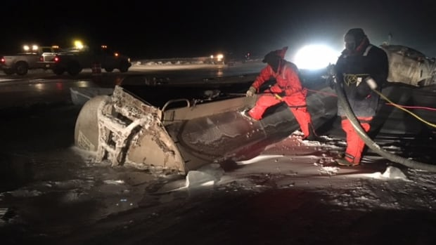 Two workers wearing floatsuits and attached to safety lines prepare to open the valve on top of a haul tanker trapped in ice on Great Bear Lake three kilometres from Deline, N.W.T., late Monday night. About 30,000 litres of fuel was extracted from the tanker over four hours.