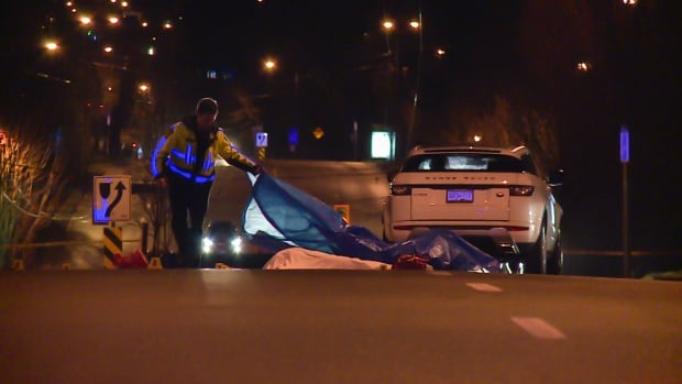 A Vancouver Police officer lays a tarp over the woman's body.