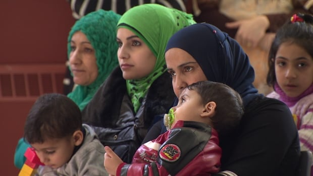 Syrian refugees listen to speakers at an orientation event held in St. John's.