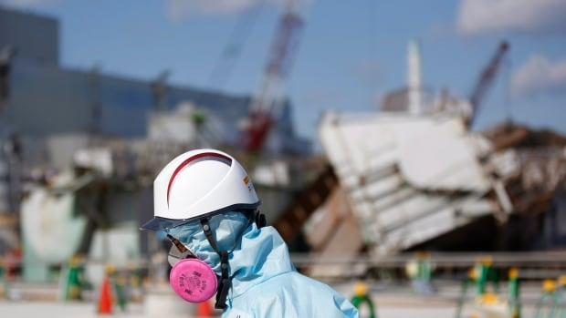 A Tokyo Electric Power Co. (TEPCO) employee, wearing a protective suit and a mask, walks in front of the No. 1 reactor building at the tsunami-crippled Fukushima Daichi nuclear power plant in Okuma, Fukushima Prefecture, northeastern Japan, on Feb. 10, 2016.