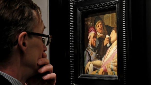 A visitor to the Galerie Talabardon & Gautier booth at the TEFAF fine art fair examines the newly discovered Rembrandt painting titled The Unconscious Patient (Sense of Smell) in Maastricht, southern Netherlands, on Thursday.