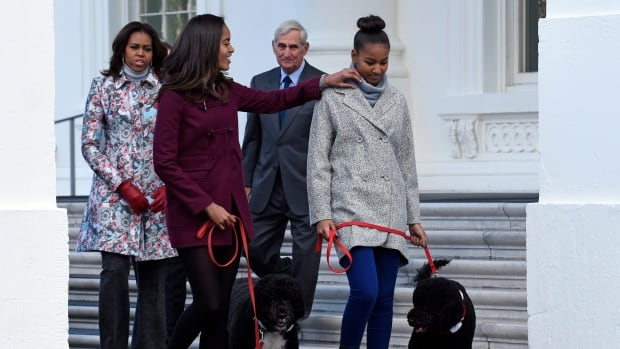 First lady Michelle Obama, left, watches as daughter Malia Obama, second from left, adjusts the collar for her sister Sasha Obama, right. Dogs Bo Obama, left, and Sunny Obama also pictured. The First family all received gifts from the Trudeaus.