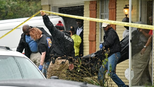 Vicksburg police carry out the body of escaped murder suspect Rafael McCloud into a coroner's vehicle on Thursday after he was shot by a homeowner during a hostage situation in Vicksburg, Miss.