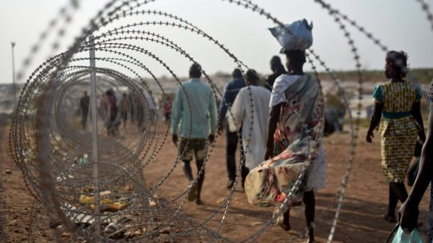 Displaced people walk next to a razor wire fence at the United Nations base in the capital Juba, South Sudan, in this Jan. 2016 photo. A UN report released Friday says groups allied to the South Sudan government were allowed to rape women in lieu of wages.