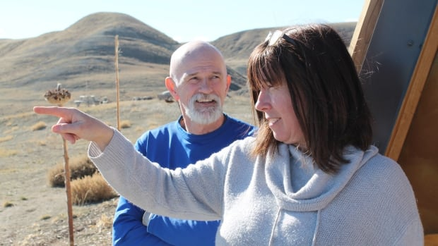 Glen and Dawn Kinney show off their property in southern Alberta. The couple has built a self-sufficient home, called an Earthship, and moved there from Calgary.