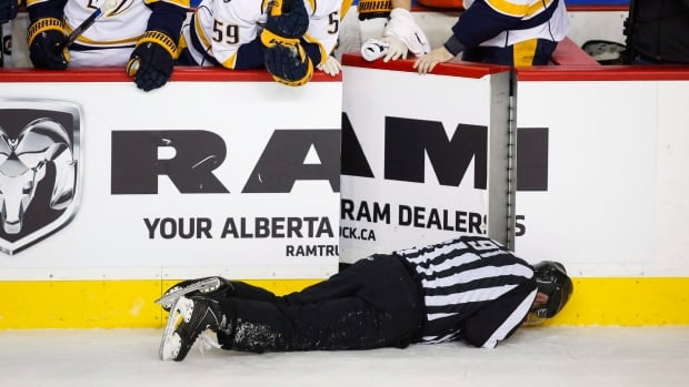 Linesman Don Henderson was hit by Calgary Flames' Dennis Wideman during the second period of a game in Calgary on Jan. 27.