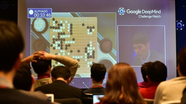 Journalists watch a big screen showing live footage of the third game of the Google DeepMind Challenge Match between Lee Se-Dol and AlphaGo at a hotel in Seoul, South Korea, on Mar. 12, 2016.