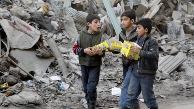 Boys carry boxes of biscuits near rubble of damaged buildings in Aleppo, Syria on March 2, 2016.