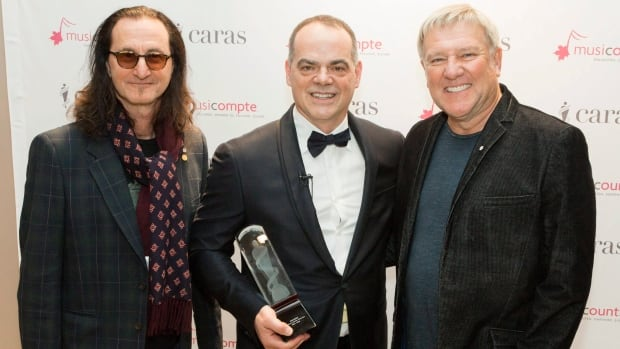 2016 MusiCounts Teacher of the Year Award recipient Don Bosse of Fredericton High School is flanked by Rush band members Geddy Lee, left, and Alex Lifeson at a recent event in Toronto.
