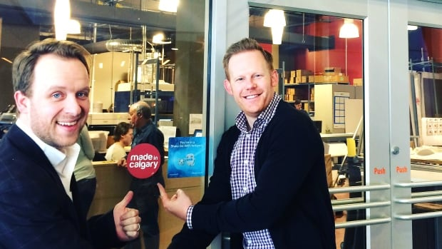 Little Rock Printers president Brian Kroeker (left) and Made in Calgary campaign co-founder Leighton Healey show off one of the red stickers.
