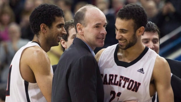 Carleton Ravens head coach Dave Smart (centre) congratulates Philip Scrubb (right) as Thomas Scrubb walks past while they celebrate defeating Ottawa to win the CIS basketball final in Toronto on March 15, 2015. Carleton enters this year's tournament with all three no longer in the mix.