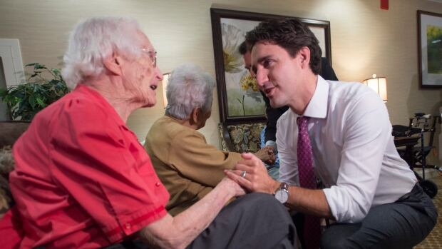 Prime Minister Justin Trudeau confirmed in an interview Thursday that next week's budget will reverse the eligibility for Old Age Security to 65 from 67. Here, Trudeau meets with residents in a Mississauga, Ont., home for seniors last October.
