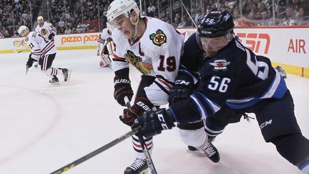 Chicago Blackhawks' Jonathan Toews (19) checks Winnipeg Jets' Marko Dano (56) during second period NHL action in Winnipeg on Friday, March 18, 2016.
