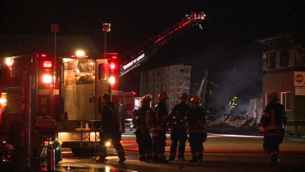 Firefighters clean up after a massive fire at a lumber yard in Langley late Friday night.