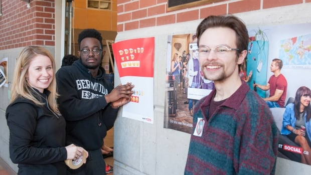 "Haley Doherty, UPEI's residence life coordinator, along with students Enesi Majebi, residence life advisor and Nathan Hood, student union vice president, place ""Keep it Social"" posters around campus."