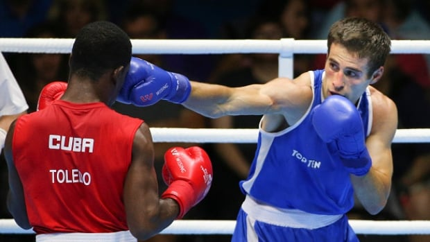 Arthur Biyarslanov (right) lands a punch on Yasnier Toledo of Cuba during the 2015 Pan Am Games in Toronto in the 64kg class.