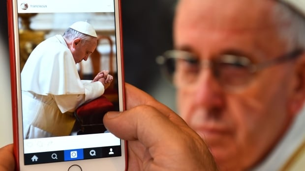 A man looks at the Instagram account of Pope Francis in Rome. The pontiff joined the photo-based social media app on Saturday.
