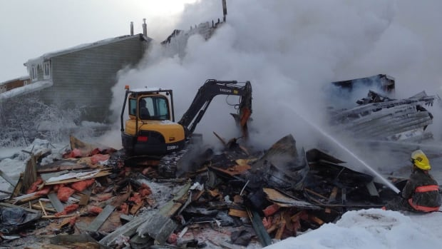 An excavator tears down part of the six-plex closest to Dolphin Street on March 19.