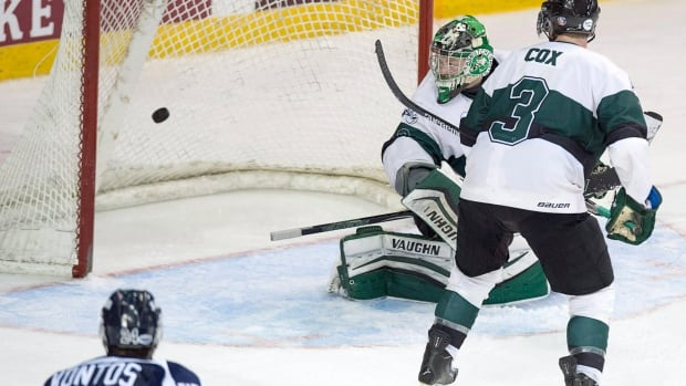 University of Saskatchewan Huskies goaltender Jordon Cooke and teammate Connor Cox watch as St. Francis Xavier X-Men Michael Clarke scores in the third overtime hockey championship action in Halifax. The X-Men won 2-1.