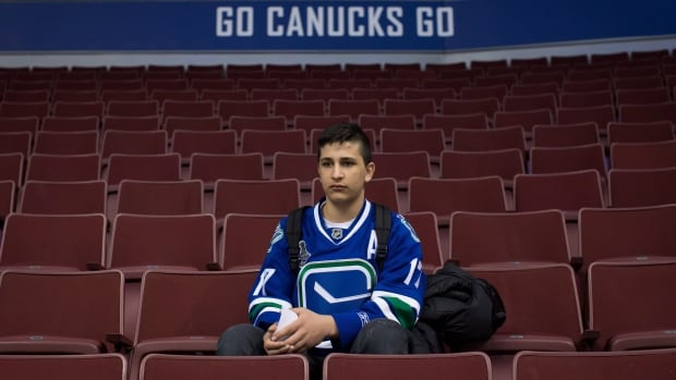 Syrian refugee Shergo Kurdi, 15, watches St. Louis Blues NHL hockey practice after a tour of Rogers Arena in Vancouver, B.C., on Saturday March 19, 2016.
