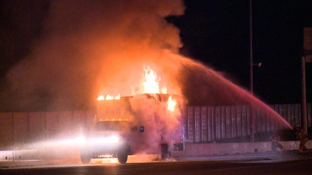 A firefighter battles flames coming from a cube van on Highway 1 in Burnaby Sunday morning.