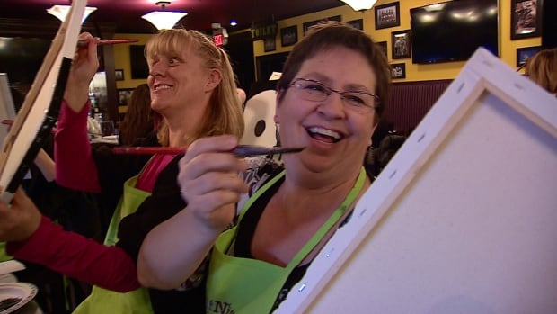 Barb Nemeth enjoys a night out at Nicastro's Pub, learning to paint a bright flower on a black backdrop at Paint Nite.