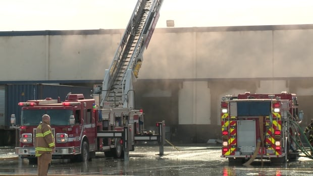 Firefighters remain on scene at a warehouse near 148th Street and 128th Avenue.
