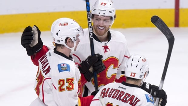 The Calgary Flames' Sean Monahan is congratulated by teammates Dougie Hamilton, centre, and Johnny Gaudreau, right, following a goal on Montreal Canadiens netminder Mike Condon on Sunday in Montreal.
