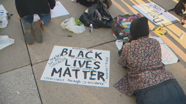A group of protesters spent the night at Toronto's Nathan Phillips Square, protesting a recent decision by Ontario's police watchdog to recommend no charges against an officer in a police shooting last summer.